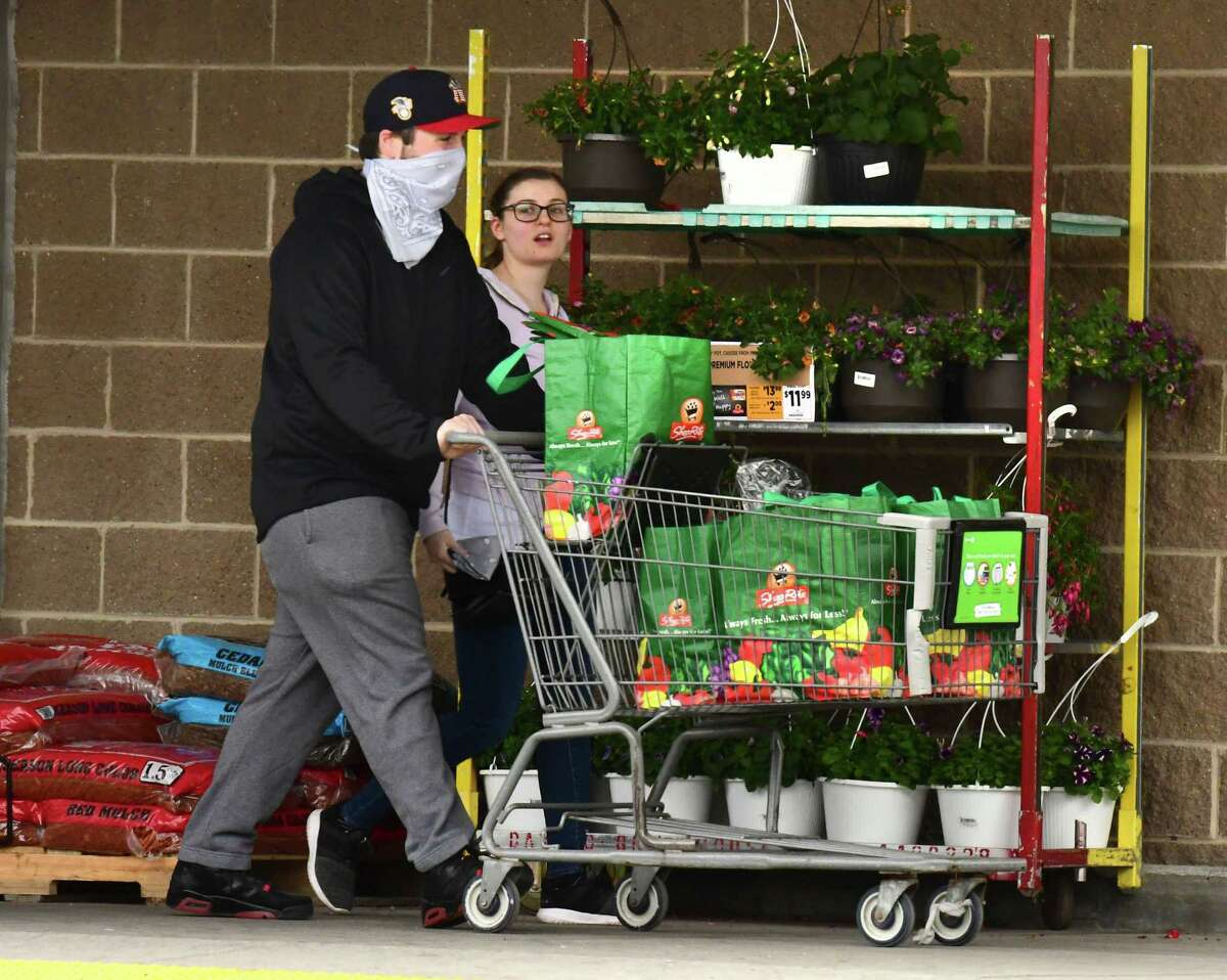 Shoppers walk out of a Shoprite with groceries on Wednesday, May 6, 2020 in Colonie, N.Y. Shoprite is one of the local grocery stores limiting beef, pork and poultry sales. (Lori Van Buren/Times Union)