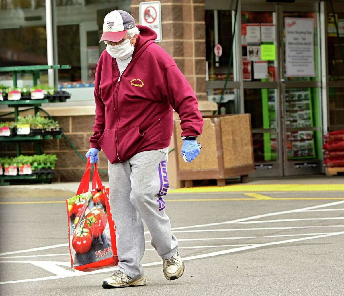 A shopper walks out of a Shoprite with groceries on Wednesday, May 6, 2020 in Colonie, N.Y. Shoprite is one of the local grocery stores limiting beef, pork and poultry sales. (Lori Van Buren/Times Union)