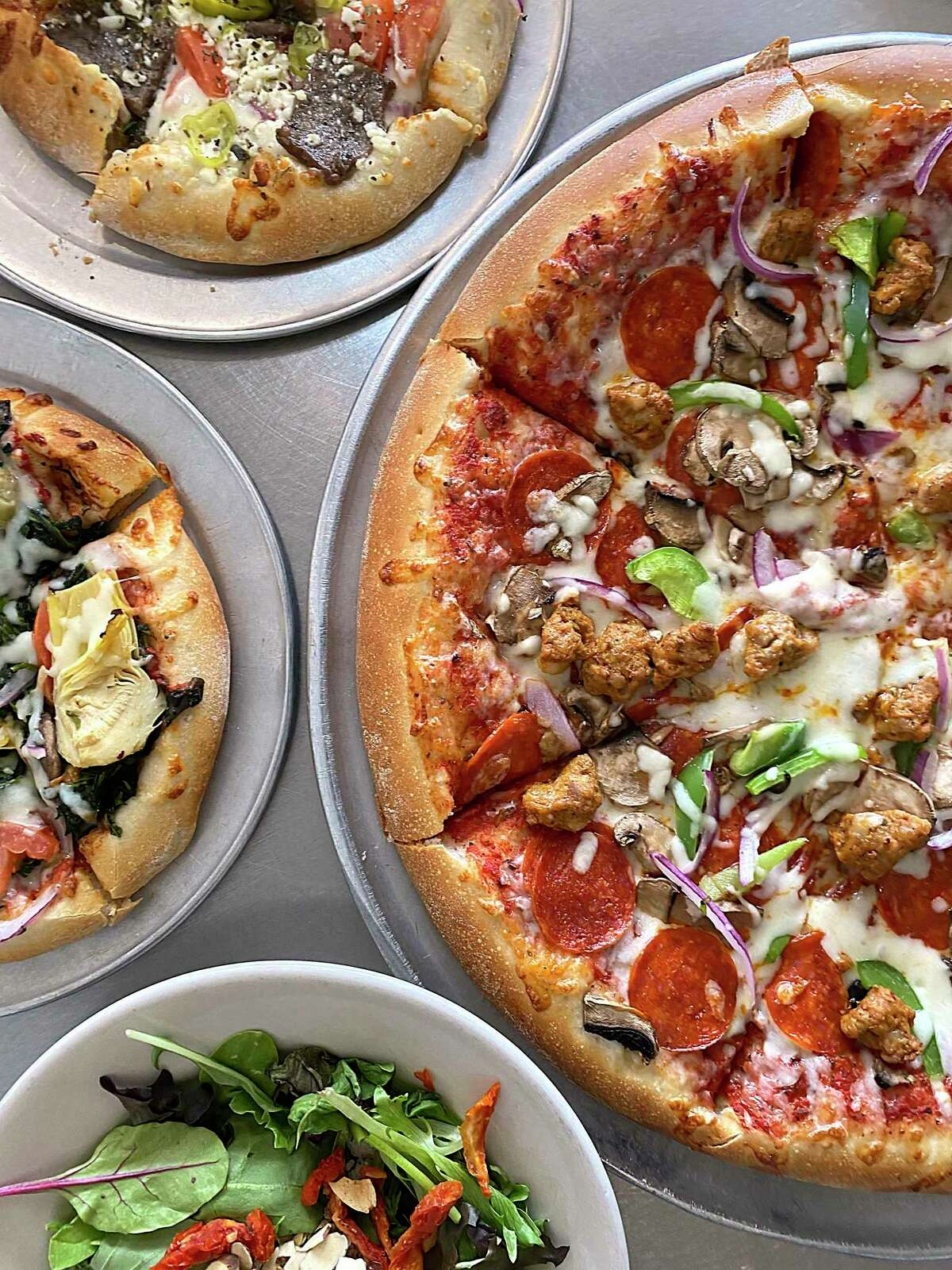 The menu includes, clockwise from top left, the Mediterranean Greek pizza, the Rome's Deluxe pizza, the Navona salad and the Vegetarian Deluxe pizza at Rome's Pizza on De Zavala Road.