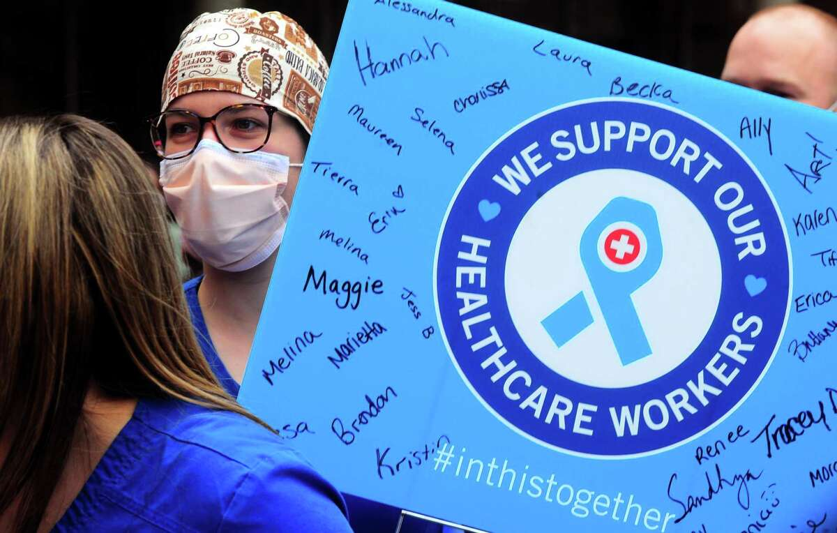 Registered nurse Kristen Cappetta holds a sign and cheers as the 1,500th patient who has recovered from COVID-19 is released from Yale New Haven Hospital in New Haven on April 29. Patient Charles Moore of New Haven was greeted by dozens of hospital workers as he was discharged.