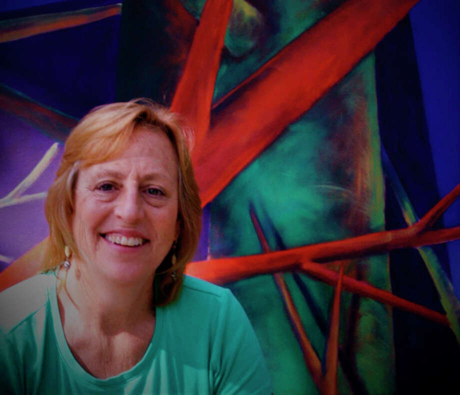 "Baldwin artist, Elisabeth Heckler-Cambridge, pictured with one of her works -- Blue Square with Fetishes -- is opening a gallery and studio in downtown Baldwin, once the ""Stay Home Stay Safe"" order is lifted. The store will feature her works, along with that of other local artists. Photo: Submitted Photo"