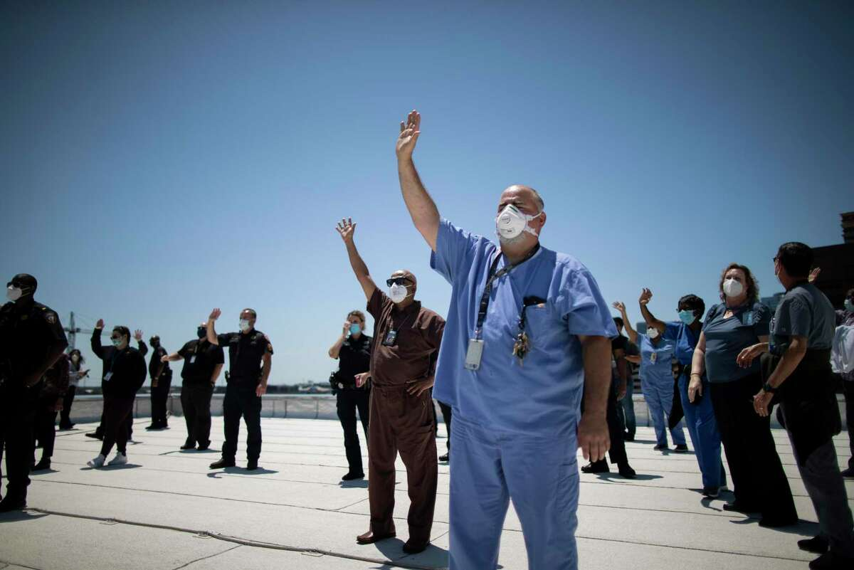 Medical staff and deputies from the Harris County Sheriff's Office observe the United States Navy's Blue Angels as they fly by from the rooftop of the Harris County Jail on Wednesday, May 6, 2020, in Houston.