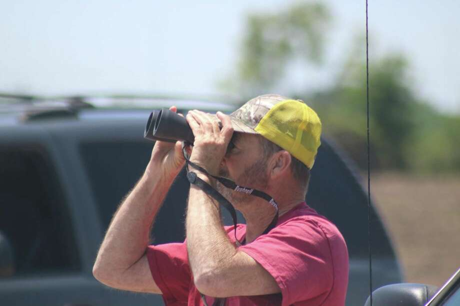 Onlookers came equipped with binoculars in preparation to watch the U.S. Navy Blue Angels fly over Ellington Airport on Wednesday afternoon. Photo: Robert Avery