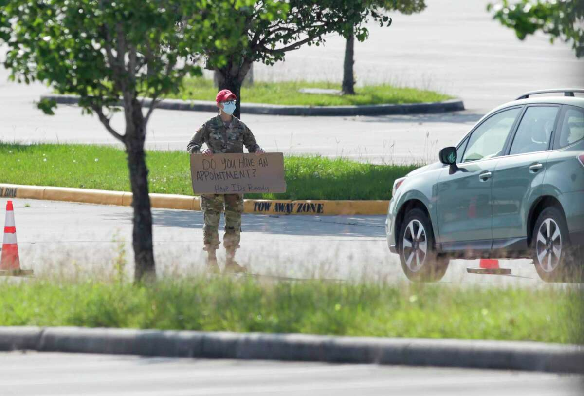 A National Guard personnel holds a sign stating, 'Do you have an appointment? Have ID's ready,' at Woodforest Bank Stadium in The Woodlands April 27. Residents will have a second chance for testing in Conroe Sunday at the Montgomery County Fair Grounds