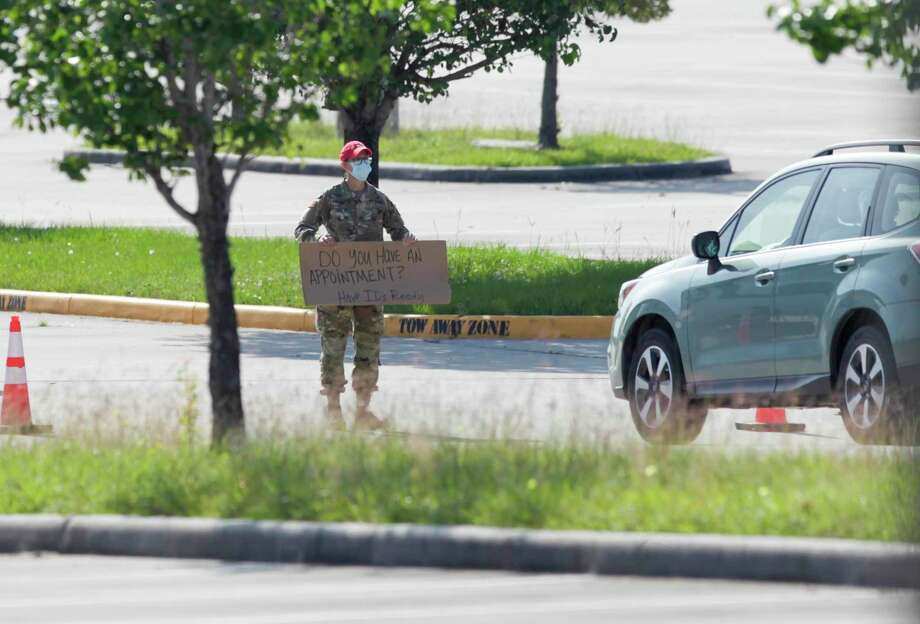 A National Guard personnel holds a sign stating, 'Do you have an appointment? Have ID's ready,' at Woodforest Bank Stadium in The Woodlands April 27. Residents will have a second chance for testing in Conroe Sunday at the Montgomery County Fair Grounds Photo: Gustavo Huerta, Houston Chronicle / Staff Photographer / Houston Chronicle © 2020