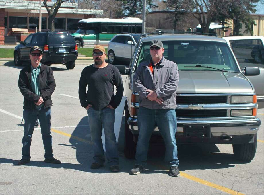 Director of Veteran Affairs Eric Sullivan, Army Veteran Jesse Hodge and Tony Covell stand in front of Hodge's Chevrolet Suburban. Manistee County Veterans Affairsraised money to return the vehicle to Hodges after it was repossessed. (Kyle Kotecki/News Advocate)