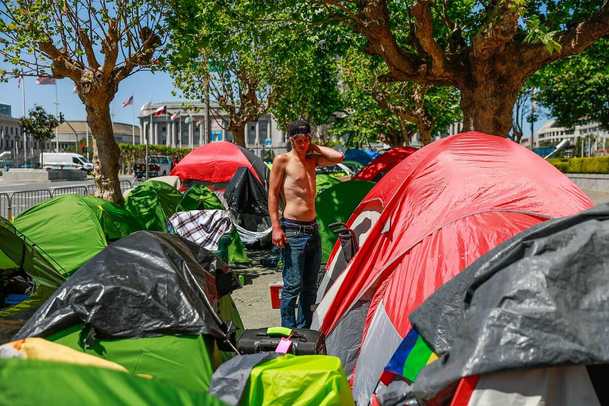 Homeless man Jacob Corbin, 30, stands in an encampment on Fulton Street on Wednesday, May 6, 2020 in San Francisco, California.