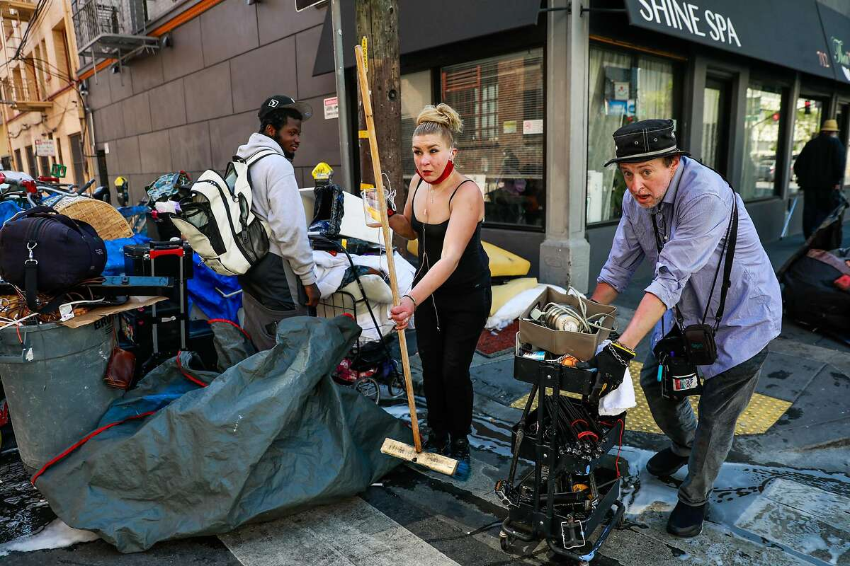Homeless couple Dashaun Jackson (left) and Tara Lowe (center) wait for street cleaning to clear Willow Street so they can set up their tent again in the Tenderloin on Wednesday, May 6, 2020 in San Francisco, California.