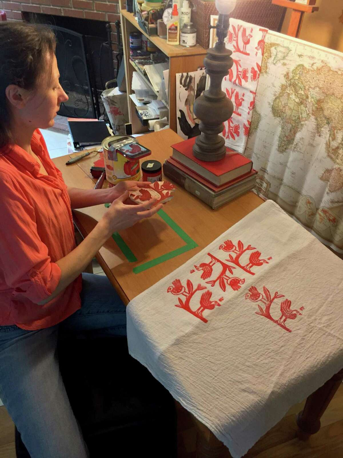 Karin Mansberg, of Bethel, records an instructional video for the beginner block printing class she'll be teaching online through Brookfield Craft Center. She stacked two cans to hold her iPhone, then taped it to the top can to record how she prints on tea towels.