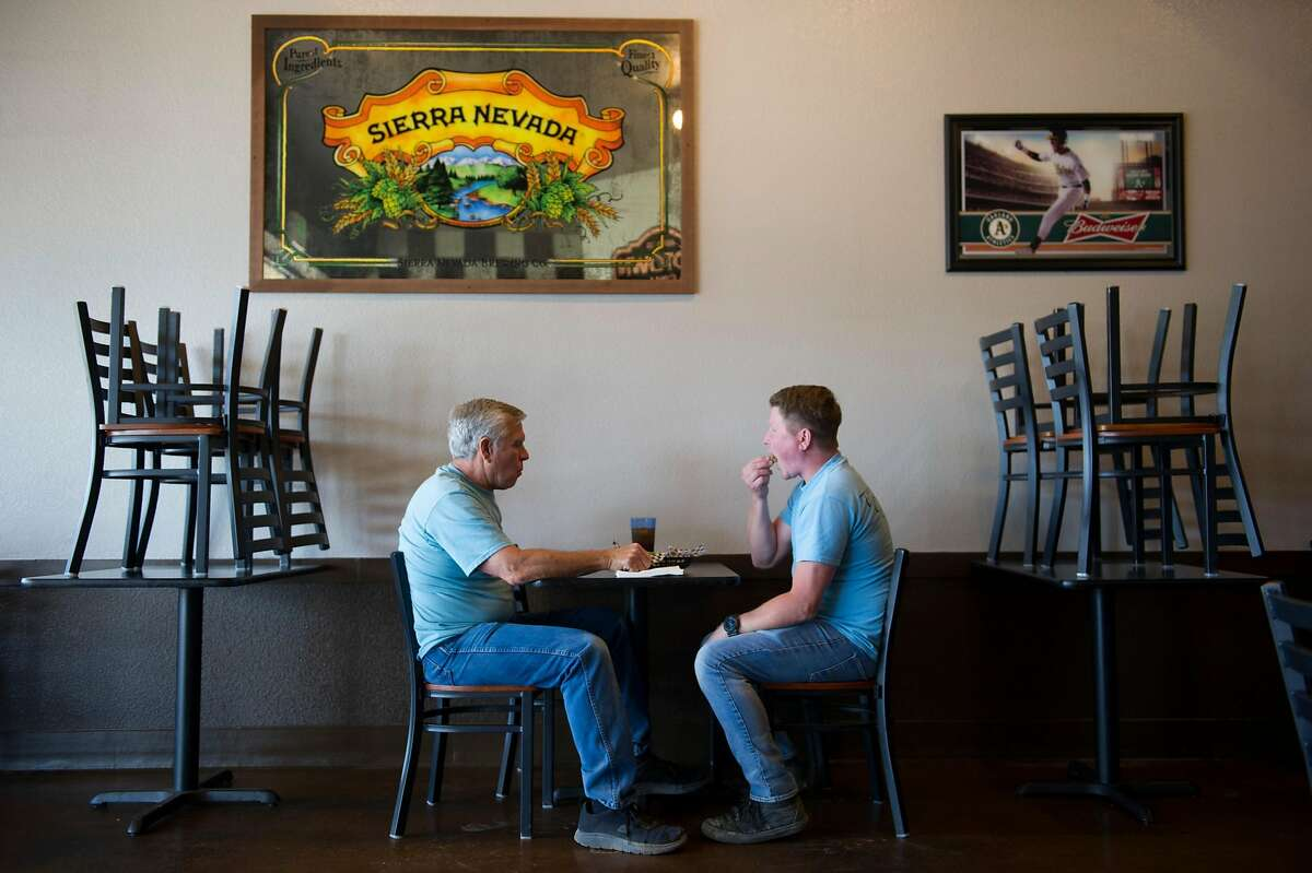 Barry Shirley, left, of Yuba City, and Curtis Liebing, of Sacramento, eat lunch at Midtown Grill in Yuba City, Calif. on Wednesday, May 6, 2020.