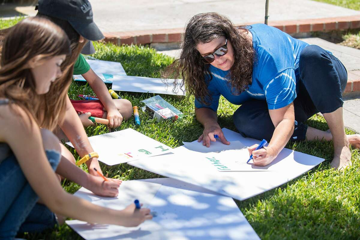"""Stefanie Duncan Fetzer, left, and her children makes signs for an upcoming """"Open California"""" rally at the California State Capital in Sacramento, on Wednesday, May 6, 2020 in their front yard in San Clemente, Calif."""