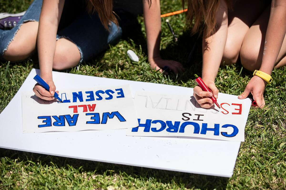 """Sisters Hallie Fetzer, 15, and Sidney Fetzer, 15, make signs for an upcoming """"Open California"""" rally at the California State Capital in Sacramento, on Wednesday, May 6, 2020 in their front yard in San Clemente, Calif."""