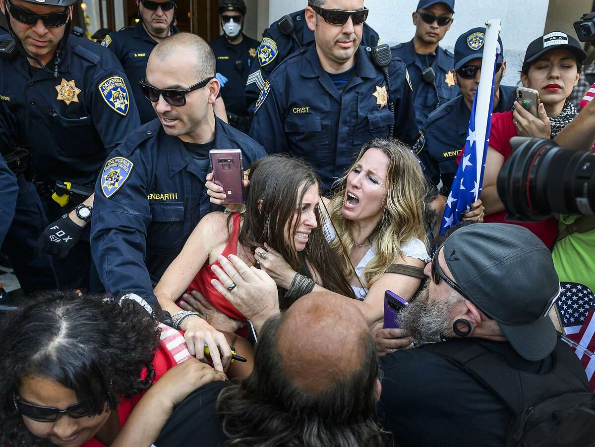 In this Friday, May 1, 2020 photo, protester Heidi Munoz Gleisner, center left, is removed from a demonstration against California Gov. Gavin Newsom's stay-at-home order by California Highway Patrol officers after they ordered a crowd of people to leave the Capitol grounds in Sacramento, Calif. (Daniel Kim/The Sacramento Bee via AP)