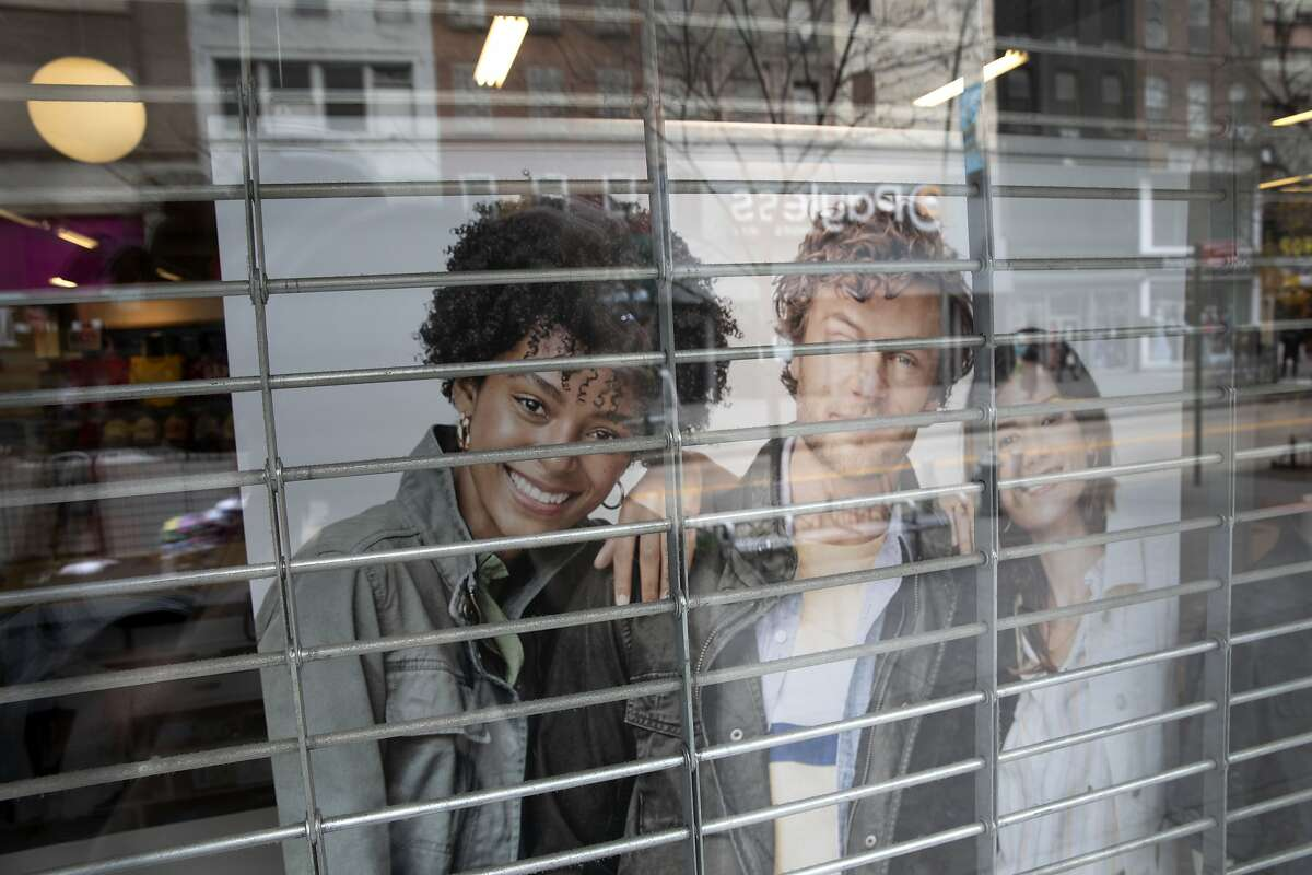In this Thursday, March 19, 2020, photo, the gate is closed on a Gap Factory Store in the Brooklyn borough of New York. The store is closed as a precaution against the spread of the coronavirus. (AP Photo/Mark Lennihan)