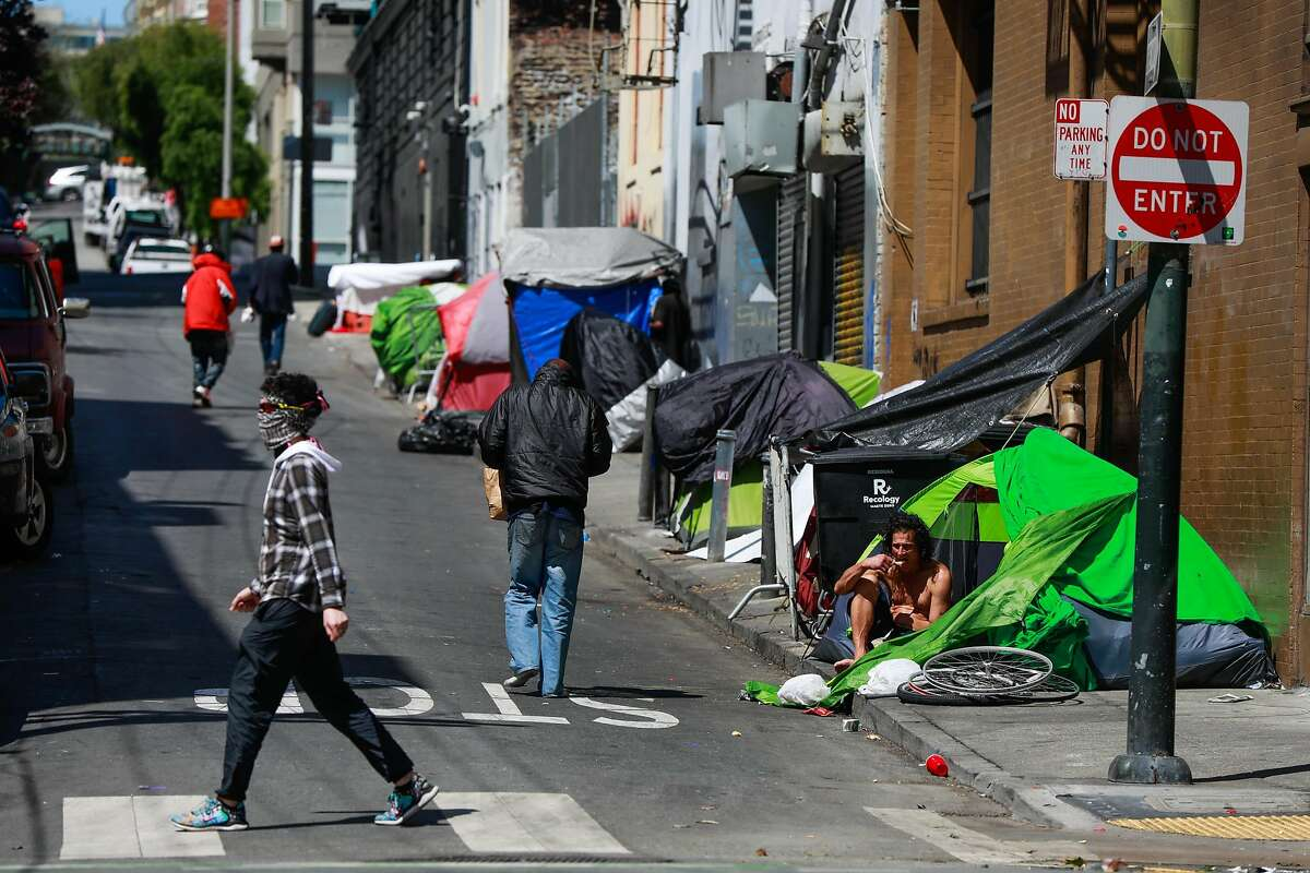 Homeless people gather on Willow Street in the Tenderloin on Wednesday, May 6, 2020 in San Francisco, California.