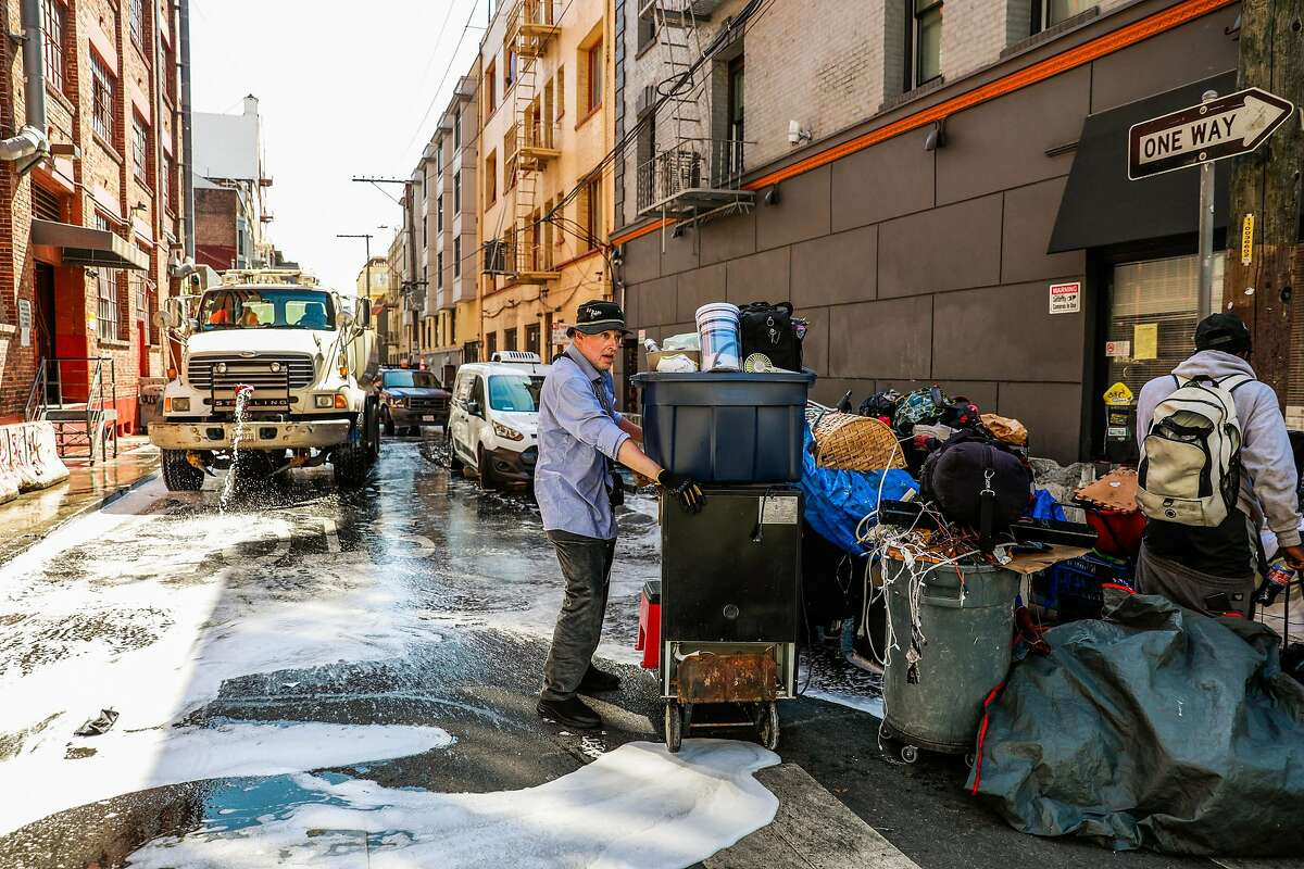 A man holds his belongings as he waits for street cleaning to clear Willow Street in the Tenderloin on Wednesday, May 6, 2020 in San Francisco, California.