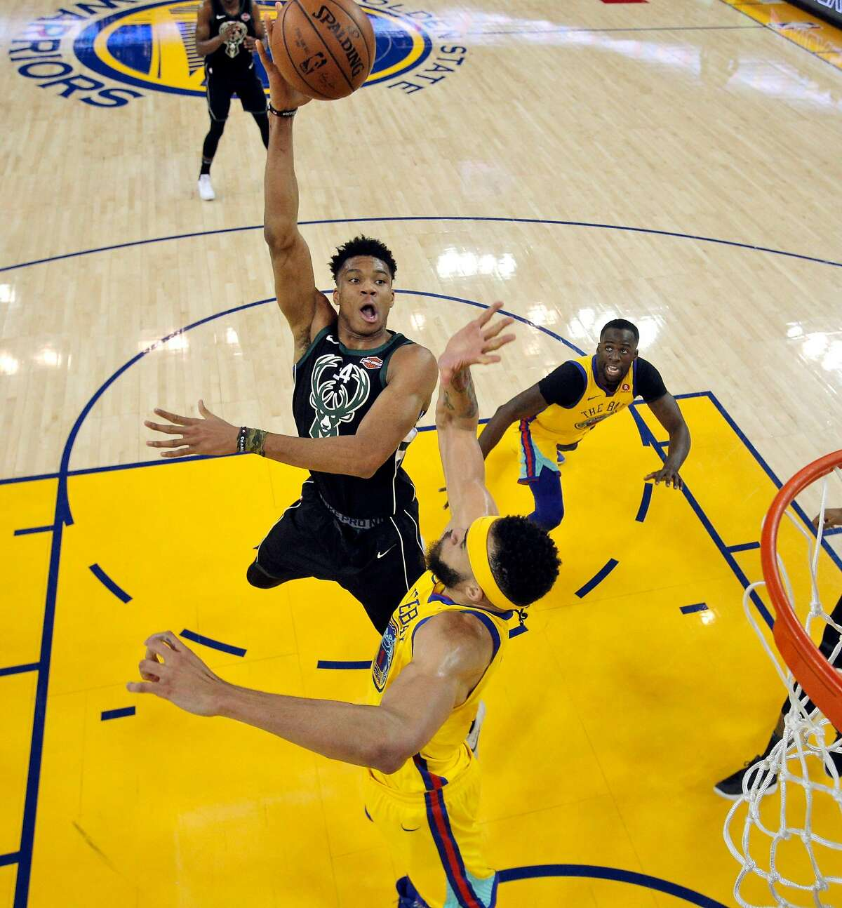 Giannis Antetokounmpo (34) puts up a shot over JaVale McGee (1) in the first half as the Golden State Warriors played the Milwaukee Bucks at Oracle Arena in Oakland, Calif., on Thursday, March 29, 2018.
