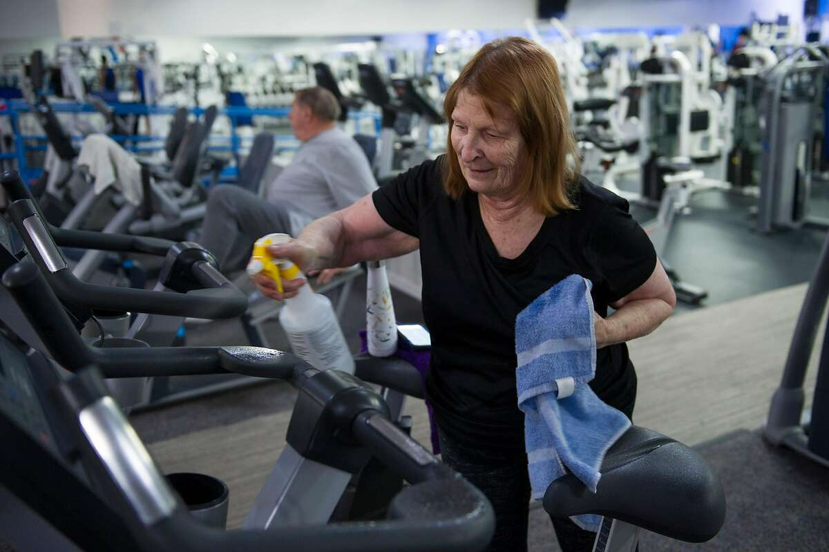 Dianne Tubandt of Yuba City sanitizes a stationary bike after exercising at Future Fitness in Yuba City, Calif. on Wednesday, May 6, 2020.
