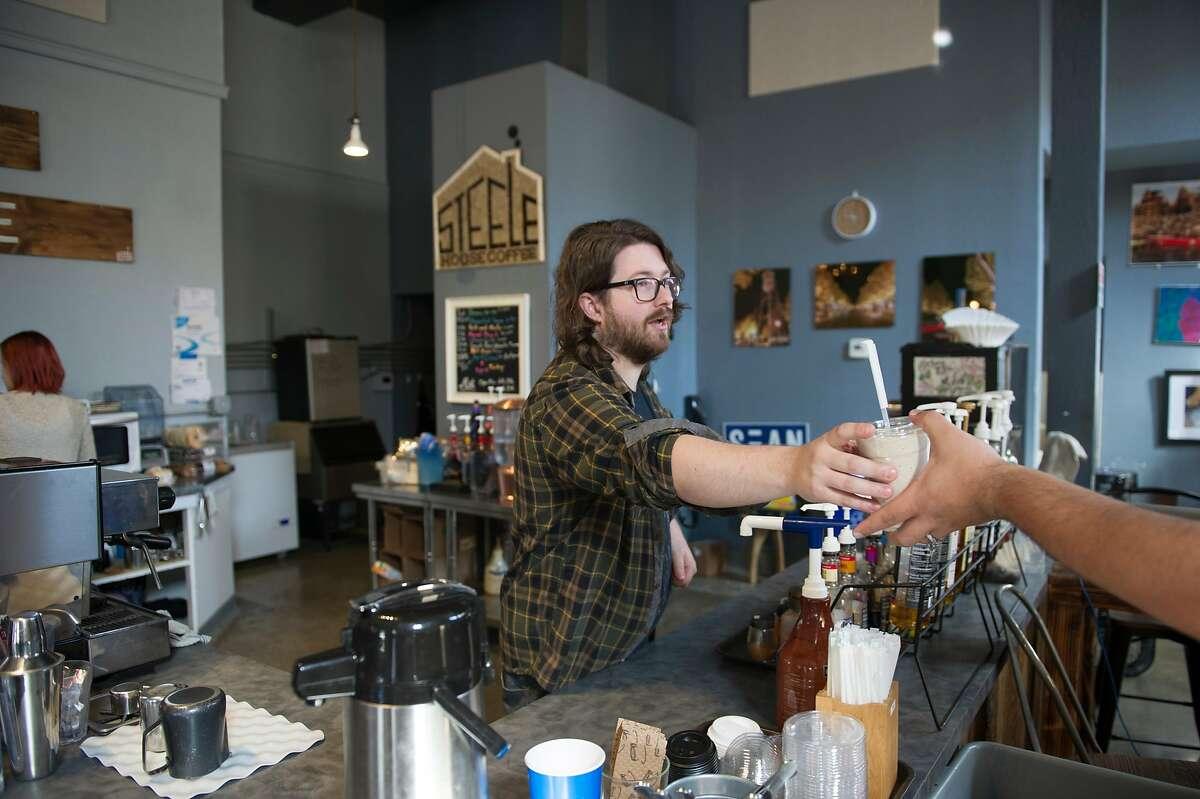 Joe Steele hands a beverage to Gabriel Gutierrez at Steele House Coffee in Yuba City, Calif. on Wednesday, May 6, 2020.