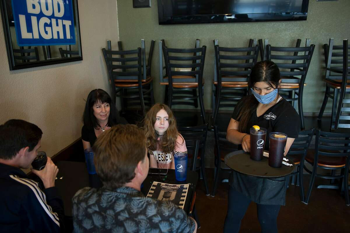Alexis Quirarte, right, brings beverages to the Epperson family of Wheatland at Midtown Grill in Yuba City, Calif. on Wednesday, May 6, 2020. They are from left: Landon Epperson, 15, Jennifer, Ryan and Olivia, 12.