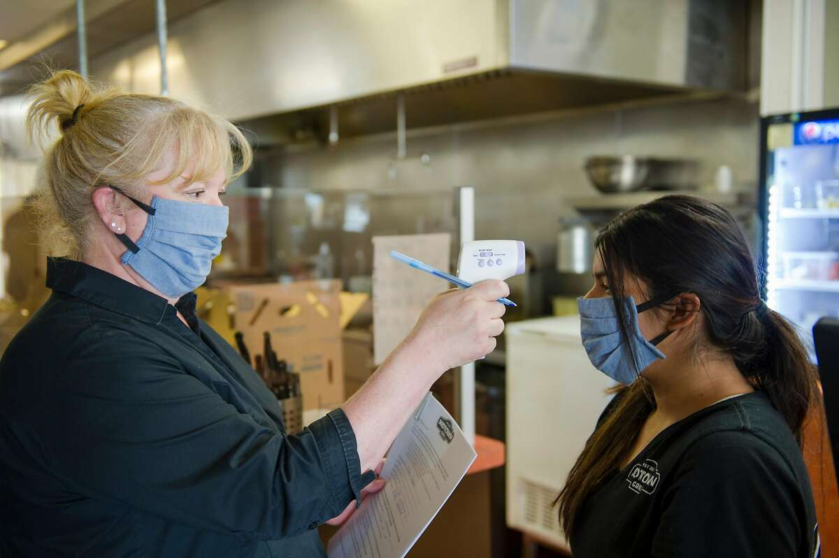 General manager Christina Hamelin, left, of Plumas Lake, checks the temperature of server Alexis Quirarte, of Yuba City, before opening the Midtown Grill in Yuba City, Calif. on Wednesday, May 6, 2020.