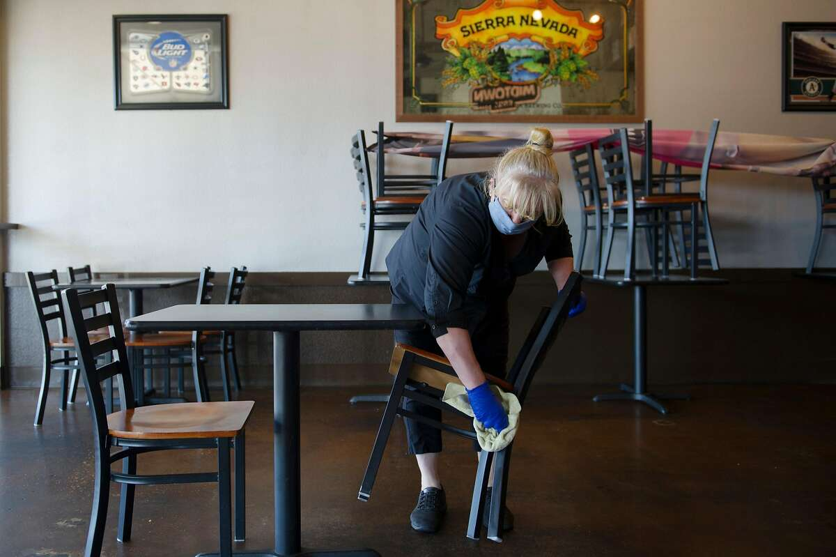 General manager Christina Hamelin of Plumas Lake sanitizes the furniture before opening the Midtown Grill in Yuba City, Calif. on Wednesday, May 6, 2020.