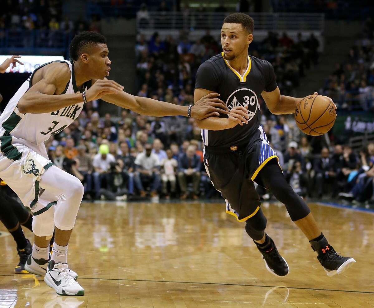 Golden State Warriors' Stephen Curry (30) dribbles against Milwaukee Bucks' Giannis Antetokounmpo during the first half of an NBA basketball game Saturday, Nov. 19, 2016, in Milwaukee. (AP Photo/Aaron Gash)