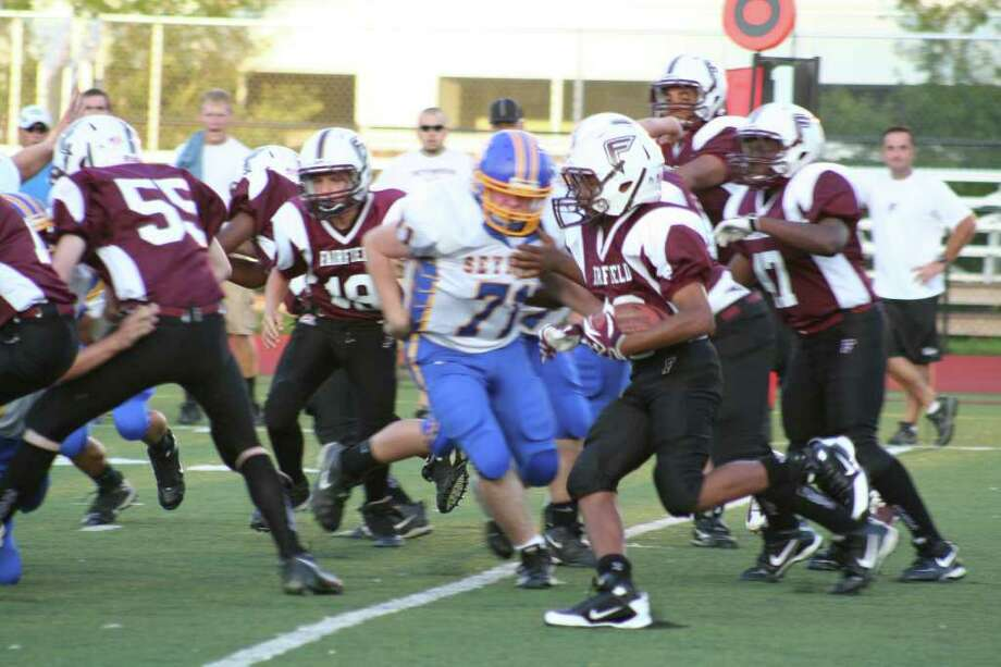 Fairfield's John Moten runs the ball against Seymour during the opening game of Pop Warner football Friday night. No. 71 from Seymour is Timothy Pereira. Photo: Contributed Photo, Contributed Photo / Tim Parry / Fairfield Citizen