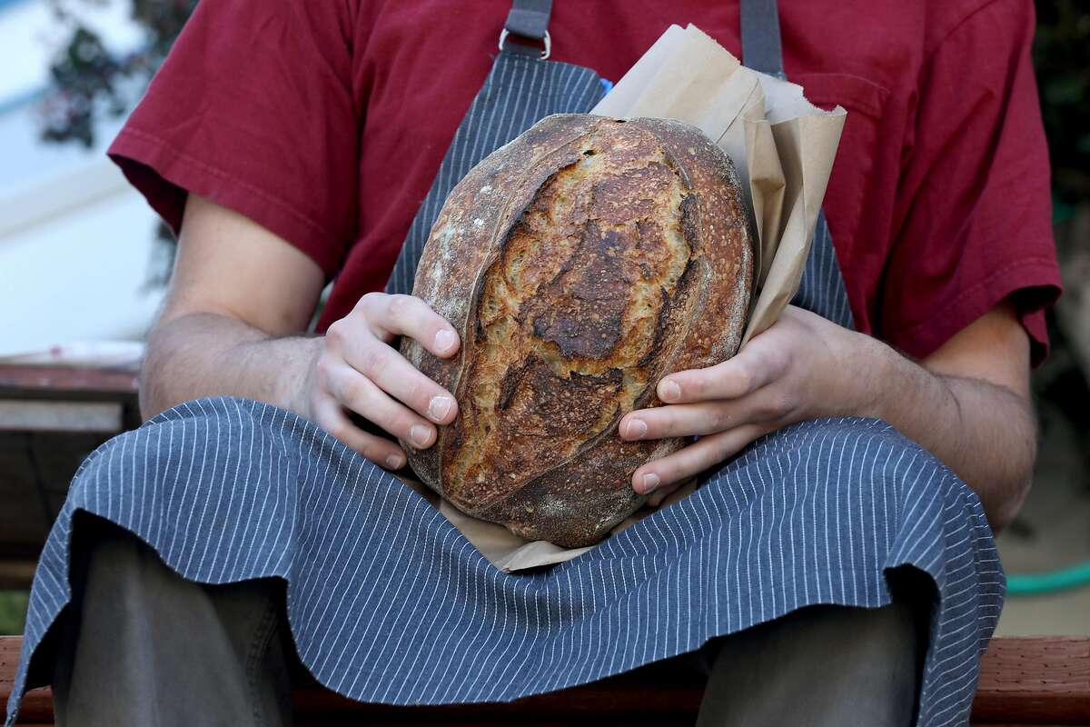 Chef Ryan Stagg holds a fresh country loaf seen at his pop-up bakery out of his home on Tuesday, May 5, 2020, in San Francisco, Calif.