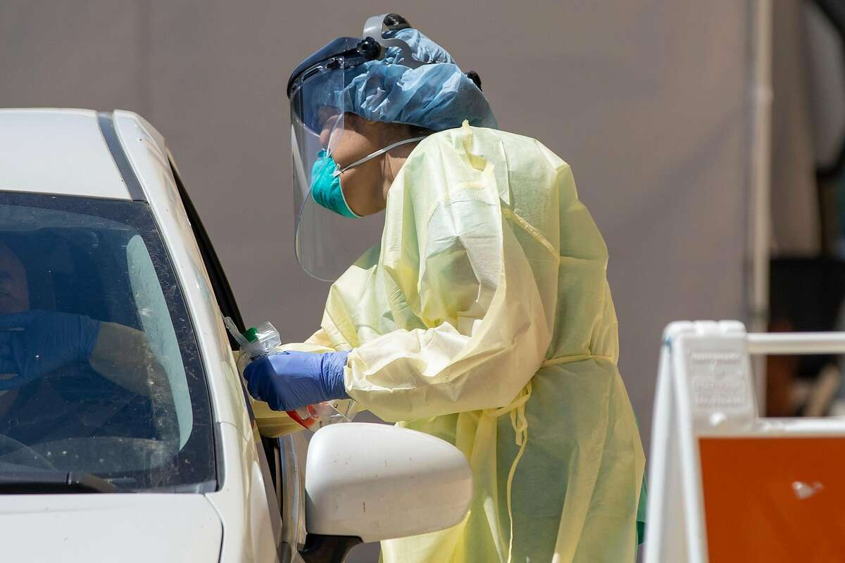 Dr. Melina Beaton wears full personal protective equipment while administering a swab test on a patient at a drive-thru Coronavirus testing site at West County Health Center in San Pablo, Calif. Friday, April 24, 2020. California Governor Gavin Newsroom Newsom says the state will need to test 60,000 to 80,000 each day in order to safely reopen society, with essential workers being tested more frequently than others. The state plans to open 86 new testing sites in