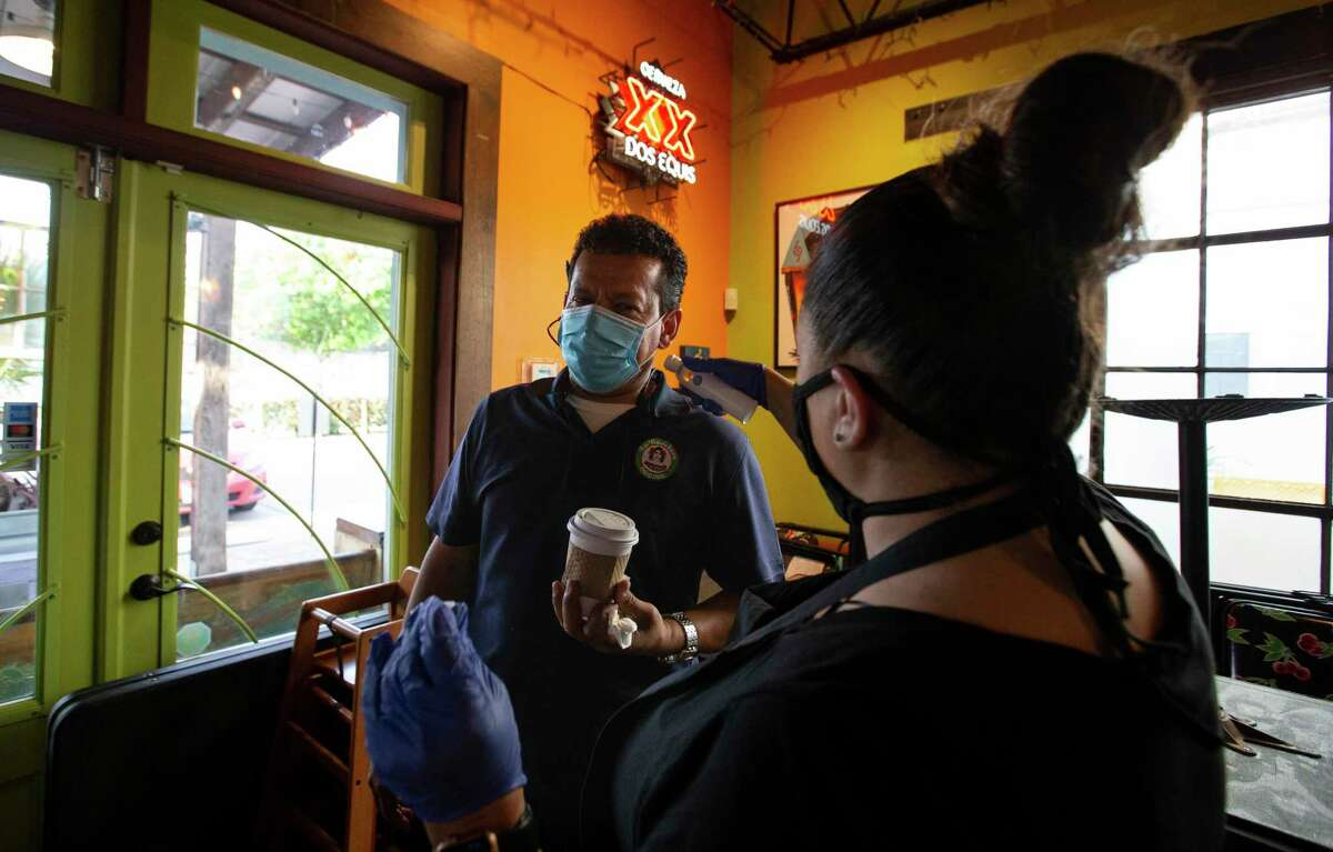 Tacos a Go Go manager Bianca Ceballos checks the temperature of Freddy Teran, who is delivering La Ranchera tortillas. Suppliers have had their orders reduced during the outbreak.