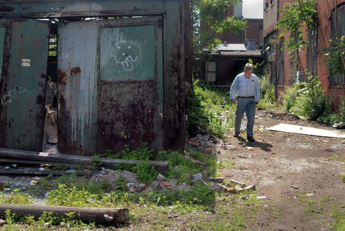 A worker looks at a brownfield site on River street in New Haven.