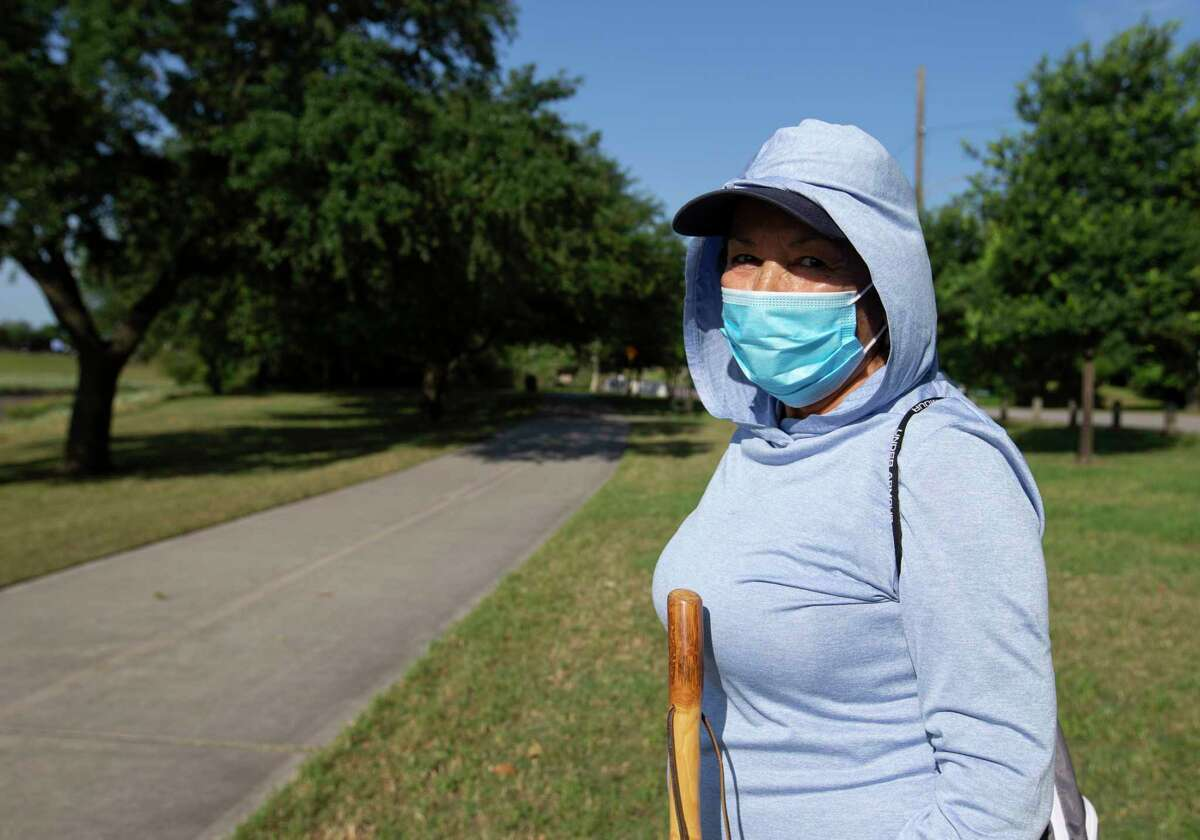 Carol Cruz wears a mask to exercise with her husband on the trail Monday, April 27, 2020, at White Oak Bayou in Houston. Harris County Judge Lina Hidalgo's order to wear face masks in public went into effect Monday. Cruz said she's been wearing masks in the public since the coronavirus outbreak because her daughter, who is a registered nurse, told her to take the virus seriously.