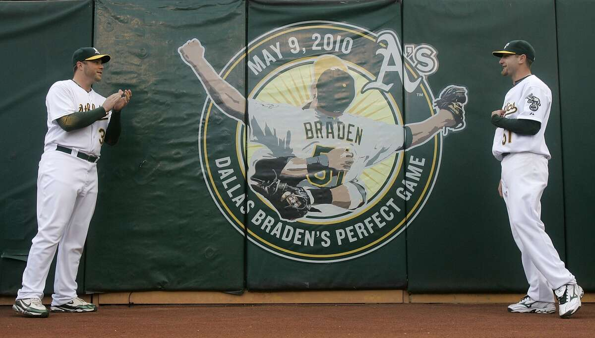 Oakland Athletics catcher Landon Powell, left, and pitcher Dallas Braden are shown near a logo commemorating Braden's perfect game before a baseball game against the San Francisco Giants in Oakland, Calif., Friday, May 21, 2010. (AP Photo/Jeff Chiu)