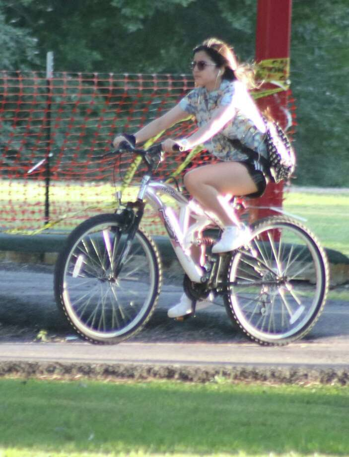This individual gets high marks for reflectors on her spokes but the ear plugs probably aren't a good idea anytime one rides a bike. Photo: Robert Avery