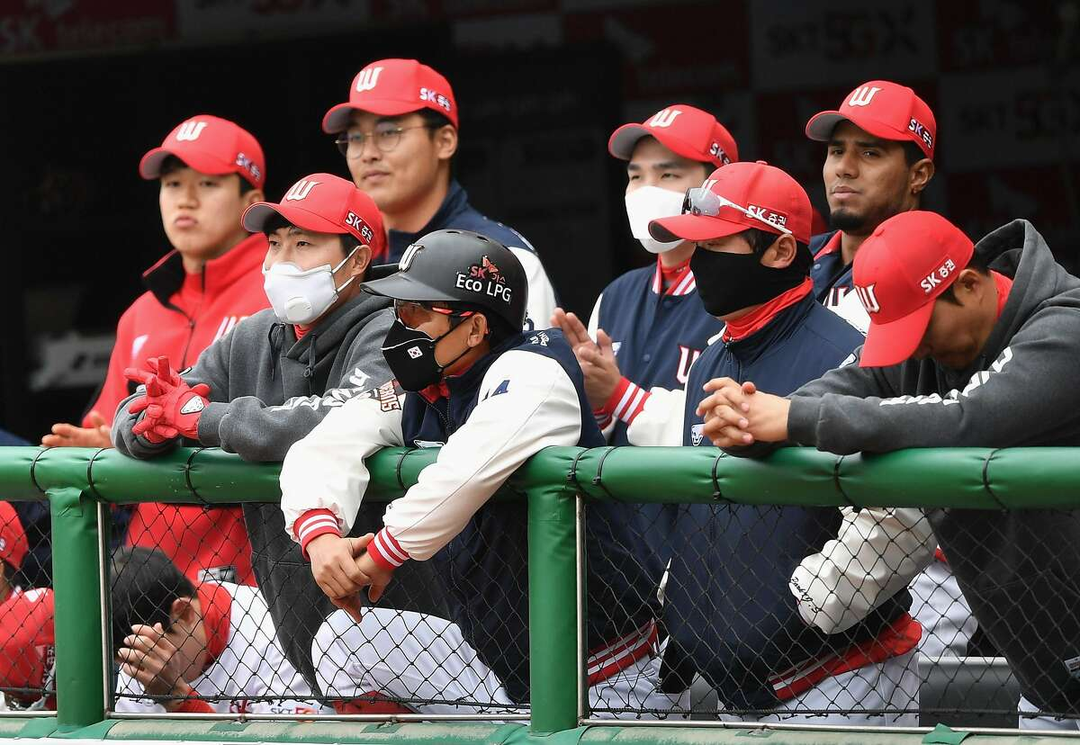 SK Wyverns players wearing face masks watch the game from the dugout during the opening game against Hanwha Eagles for South Korea's new baseball season at Munhak Baseball Stadium in Incheon on May 5, 2020. - South Korea's professional sport returned to action on May 5 after the coronavirus shutdown with the opening of a new baseball season, while football and golf will soon follow suit in a ray of hope for suspended competitions worldwide. (Photo by Jung Yeon-je / AFP) (Photo by JUNG YEON-JE/AFP via Getty Images)