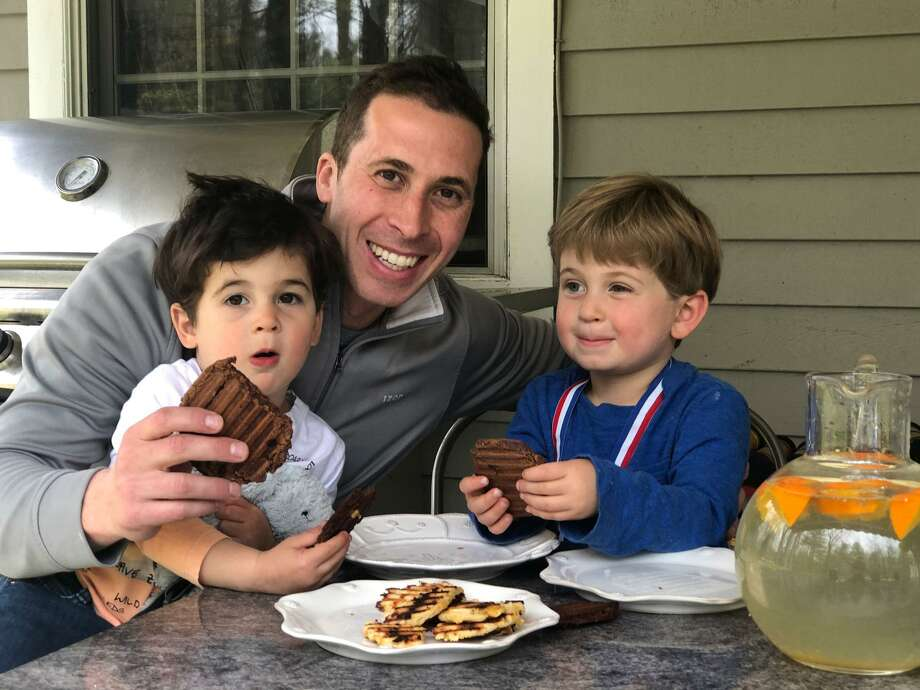 Michael Fensterstock of Wilton and sons Blaire, 2, and Parker, 3, enjoy chocolate arepas, one of three flavors of arepas being sold by Fensterstock's door-to-door business alldaysnacks.com. Photo: Contributed Photo