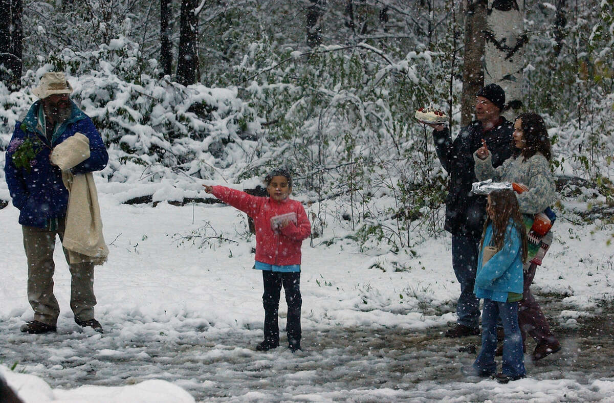 A young girl points the way through the snow as people make thier way to a Flower Festival and Hiroshima Flame ceromony at the Grafton Peace Pagoda in Grafton, New York Saturday May 17, 2002.