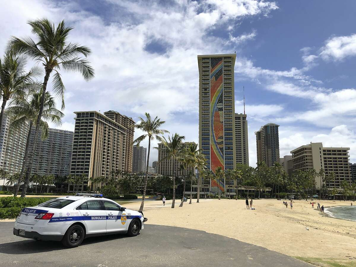 A police officer arrives to tell people to leave Waikiki Beach in Honolulu. Hawaii law enforcement authorities are cracking down on rogue tourists who are visiting beaches, jetskiing, shopping and generally flouting strict requirements that they quarantine for 14 days after arriving. (AP Photo/Caleb Jones, File)