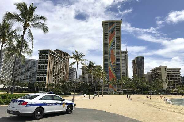 FILE - In this March 28, 2020, file photo, a police officer arrives to tell people to leave Waikiki Beach in Honolulu. Hawaii law enforcement authorities are cracking down on rogue tourists who are visiting beaches, jetskiing, shopping and generally flouting strict requirements that they quarantine for 14 days after arriving. (AP Photo/Caleb Jones, File)