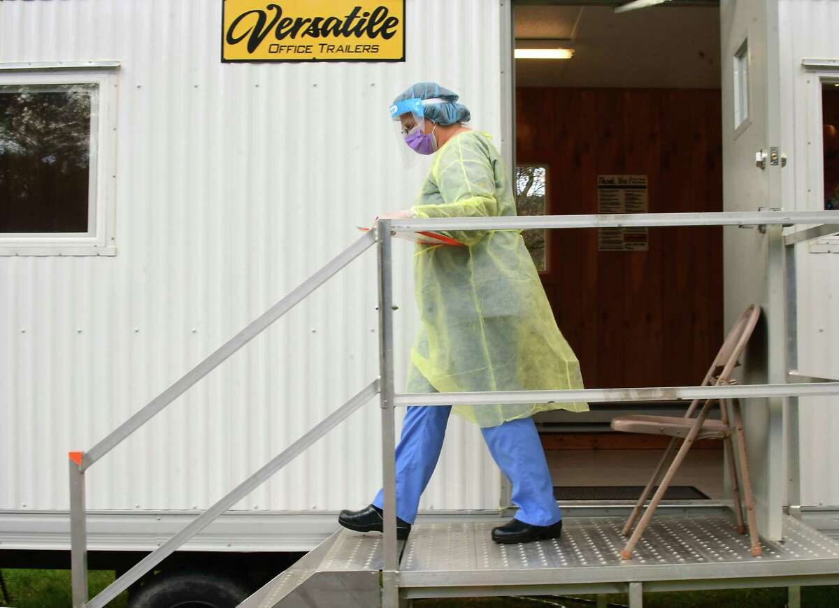 A healthcare worker leaves a trailer to greet a patient at a COVID-19 testing site behind Warren County Municipal Center on Thursday, May 7, 2020 in Queensbury, N.Y. (Lori Van Buren/Times Union)