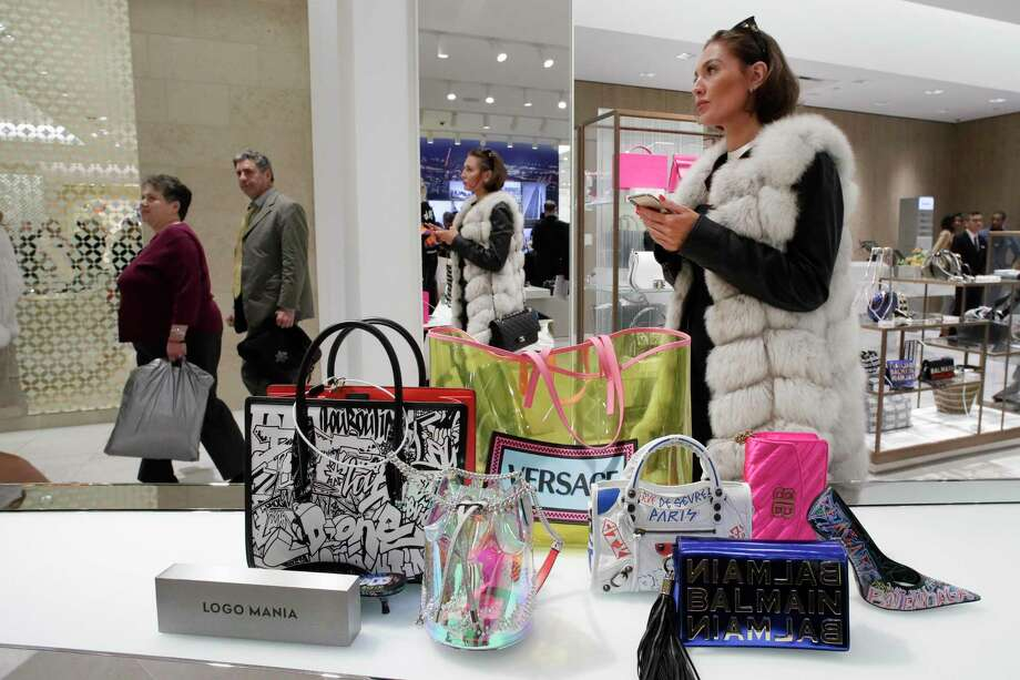 FILE- In this March 14, 2019, file photo a woman shops at Neiman Marcus during the opening night of The Shops & Restaurants at Hudson Yards in New York. Luxury department stores like Neiman Marcus and Saks Fifth Avenue once ruled among the affluent set. Now, they're fighting a tough battle to lure younger shoppers faced with a lot more shopping choices, including second-hand retailers and fashion rental companies. (AP Photo/Mark Lennihan, File) Photo: Mark Lennihan / Associated Press / Copyright 2019 The Associated Press. All rights reserved.