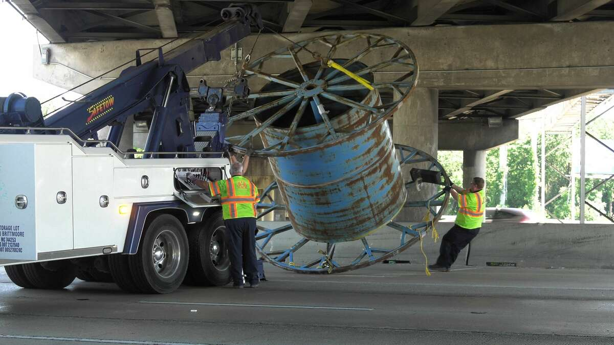 Houston police and wreckers remove loose spools from the Katy Freeway at Houston Avenue on Thursday, May 7, 2020.