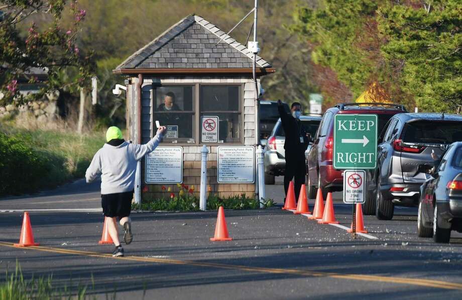 Cars line up at the gate as a jogger shows his park pass during the reopening of Greenwich Point Park in Old Greenwich, Conn. Thursday, May 7, 2020. Photo: Tyler Sizemore / Hearst Connecticut Media / Greenwich Time
