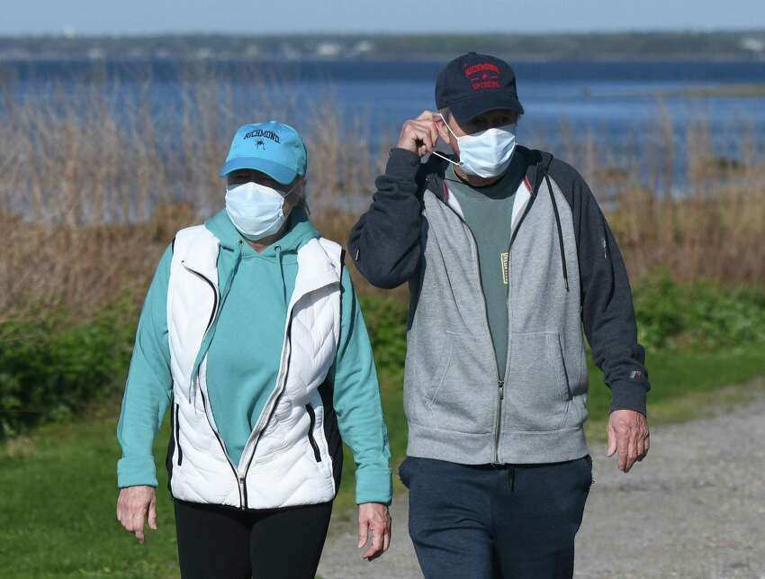 Jill and Jerry Beddall wear masks while walking a trail at the reopening of Greenwich Point Park in Old Greenwich, Conn. Thursday, May 7, 2020.
