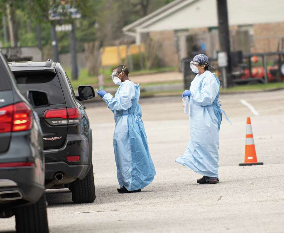 Latonya Johnson, left, working a drive through testing site at UT Physicians. Photo: Kim Kham Photos