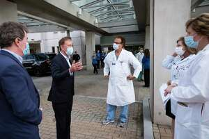 Connecticut Gov. Ned Lamont, left, talks with medical staff outside Saint Francis Hospital, Thursday, May 7, 2020 in Hartford, Conn. He made a visit to the medical center to thank the healthcare workers for their efforts during the coronavirus pandemic. (AP Photo/Mark Lennihan)