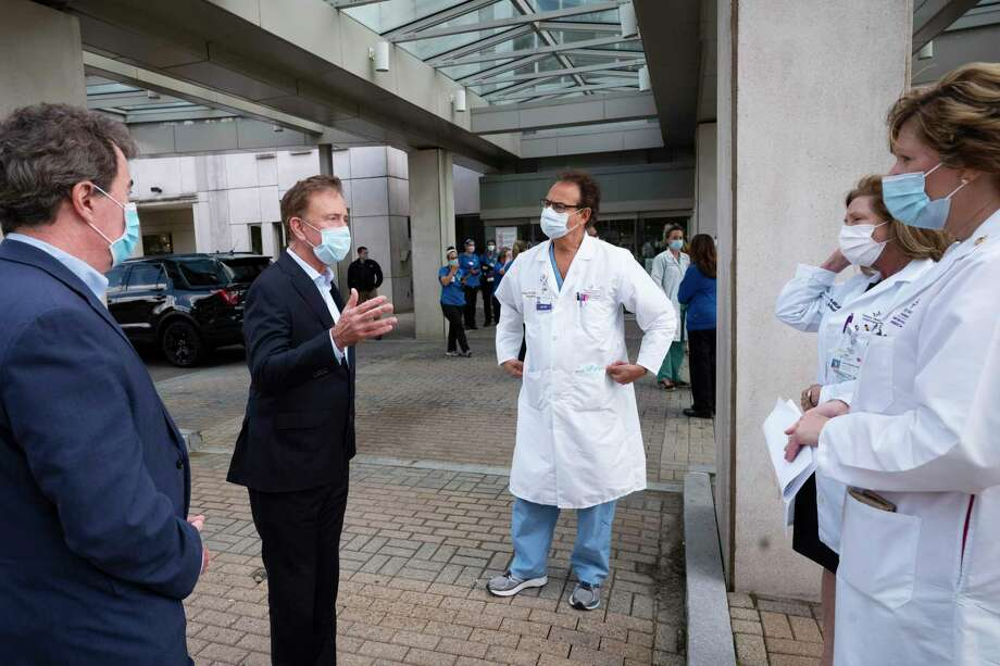 Gov. Ned Lamont, left, talks with medical staff outside Saint Francis Hospital on Thursday in Hartford. Photo: Mark Lennihan / Associated Press / Copyright 2020 The Associated Press. All rights reserved