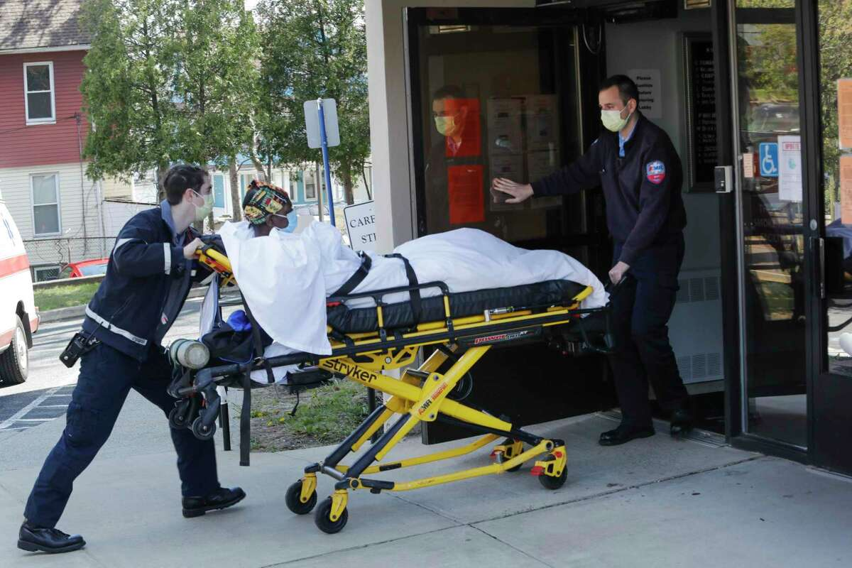 Medical workers bring a patient to the Northbridge Health Care Center in Bridgeport in April.