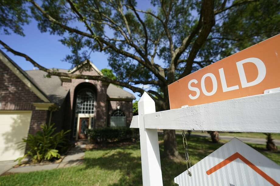 A sold sign is shown on a real estate sign outside a home Tuesday, March 31, 2020. Photo: Melissa Phillip, Staff Photographer